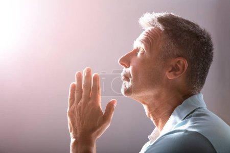 Faithful Mature Man Praying Under A Divine Light