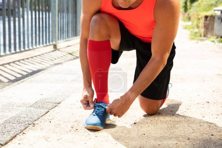 Male Athlete Tying Shoelace Getting Ready For Jogging