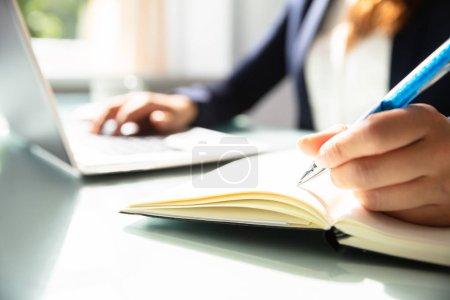 Photo pour Gros plan de la note d'écriture à la main d'une femme d'affaires avec stylo dans le journal intime sur le bureau - image libre de droit