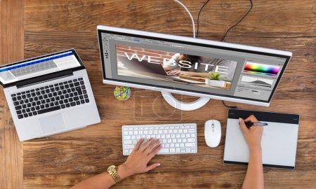 Main du concepteur femelle lors de la création de site Web sur l'ordinateur à l'aide de tablette graphique
