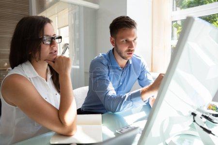 Photo pour Deux hommes d'affaires jeunes professionnels regardant ordinateur ayant la Conversation au lieu de travail - image libre de droit