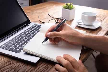 Photo pour Écriture de main de personne sur le cahier noir utilisant le stylo sur l'ordinateur portable - image libre de droit