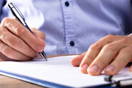 Close-up Of A Businessman's Hand Signing Contract Papers