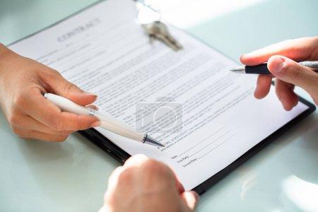 Photo pour Gros plan O un Agent immobilier à aider le Client à remplir le formulaire de contrat - image libre de droit