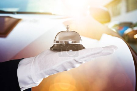 Photo for Close-up Of A Person's Hand Holding Service Bell In Front Of Car - Royalty Free Image