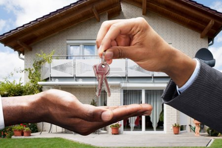 Photo for Close-up Of Real Estate Agent Giving Key To Client In Front Of House - Royalty Free Image
