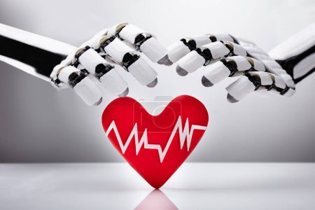 Close-up Of A Robotic Hand Protecting Red Heart With Pulse Rate