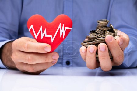 Close-up Of A Man's Hand Holding Red Heart With Pulse Rate And Golden Coins