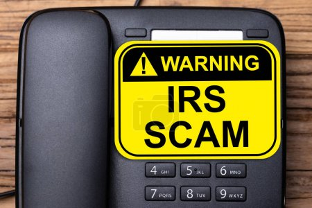 Elevated View Of IRS Scam Warning Sign On Black Landline Phone