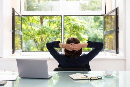 Photo pour Femme d'affaires décontractée avec les mains derrière la tête, assis dans le bureau - image libre de droit