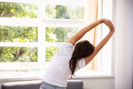Photo pour Femme étirant ses bras devant la fenêtre - image libre de droit