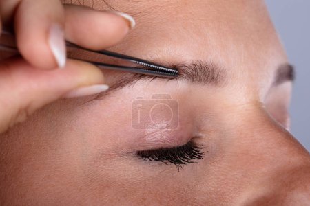 Photo for Close-up Of A Female Hand Plucking Her Eyebrow Hair With Tweezers - Royalty Free Image