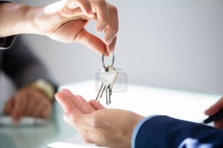 Close-up Of An Estate Agent's Hand Giving House Key To Man