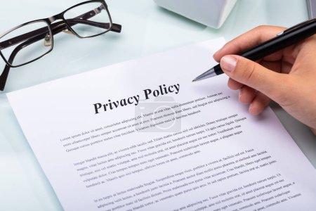 Photo pour Gros plan de la main d'une femme tenant un stylo sur le formulaire de politique de confidentialité - image libre de droit