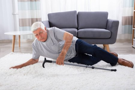 Photo for Senior Man Fallen On Carpet With Walking Stick - Royalty Free Image