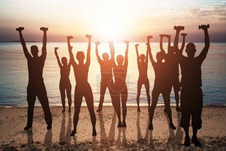 Photo pour Silhouette de personnes s'exerçant avec des haltères sur la plage au crépuscule - image libre de droit