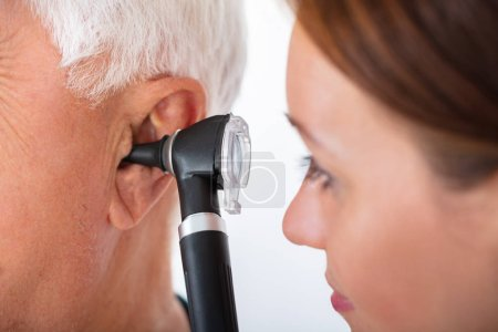 Photo for Close-up Of A Female Doctor Examining Senior Male Patient's Ear With Otoscope - Royalty Free Image