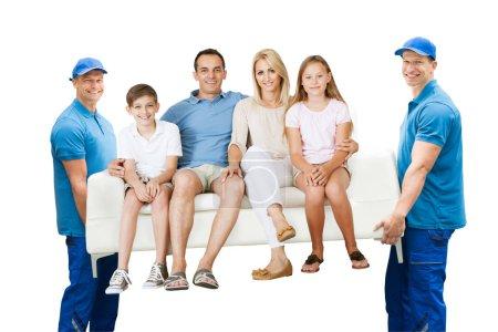 Feliz macho se mueve llevando sofá con la familia sobre fondo blanco