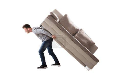 Photo pour Vue latérale d'un jeune homme portant un canapé sur fond blanc - image libre de droit