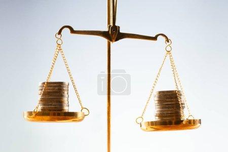 Photo pour Gros plan des pièces empilées d'or à l'échelle de la justice - image libre de droit