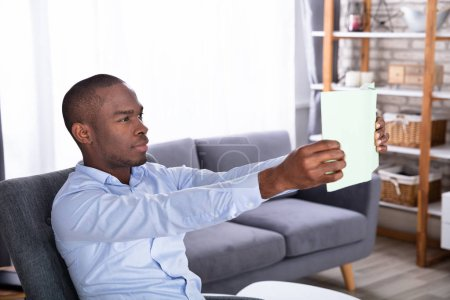 Photo for Side View Of A Young African Man Holding Book - Royalty Free Image