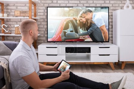 Photo for Man Streaming Television Channel Through Wireless Connection On Digital Tablet - Royalty Free Image
