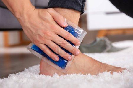 Photo pour Gros plan d'un homme qui applique du gel glacé sur une cheville blessée - image libre de droit