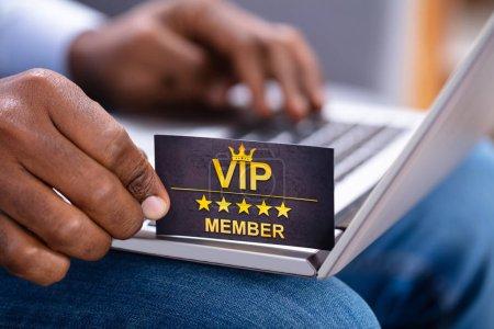 Photo pour Gros plan de la main d'un homme tenant une carte de membre VIP tout en utilisant un ordinateur portable - image libre de droit
