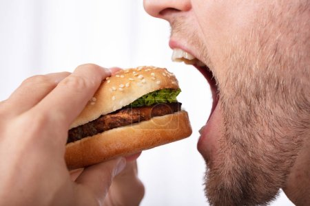 Photo for Close-up Of A Young Man Eating Fresh Burger - Royalty Free Image