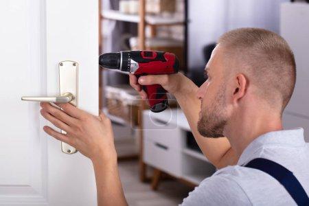 Photo pour Carpenter mâle installation serrure de porte avec un tournevis sans fil - image libre de droit