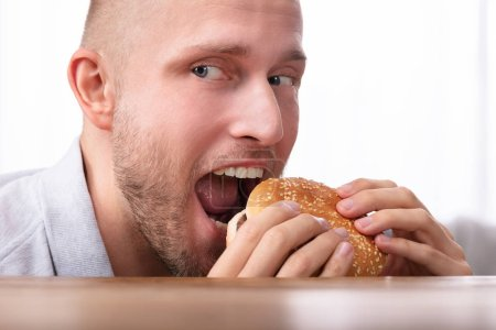 Photo for Portrait Of A Greedy Young Man Eating Burger - Royalty Free Image