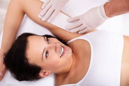 Photo pour Main d'esthéticienne épilation souriant aisselle féminine avec la bande de cire - image libre de droit