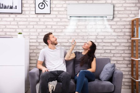 Photo for Happy Young Couple Sitting On Sofa Operating Air Conditioner At Home - Royalty Free Image