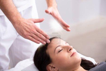 Photo pour Gros plan d'une main du thérapeute donnant Reiki guérison traitement pour femme en Spa - image libre de droit