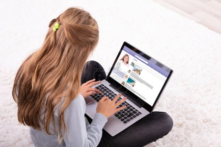 Photo pour Gros plan d'une fille utilisant le site de réseautage social sur un ordinateur portable à la maison - image libre de droit