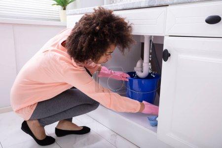 Photo pour Gros plan d'une jeune femme plaçant seau bleu sous l'eau, une fuite de canalisation de l'évier - image libre de droit
