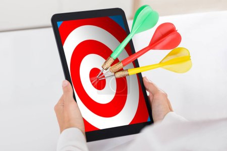 Photo for Human Hand Holding Digital Tablet With Colorful Darts On Target Over White Desk - Royalty Free Image