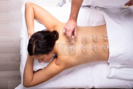 Photo pour Relaxé jeune femme recevant Cupping traitement sur son dos dans le spa - image libre de droit
