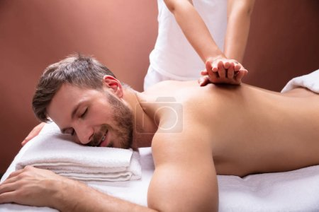 Close-up Of Therapist Hand Giving Back Massage To Young Man In Spa
