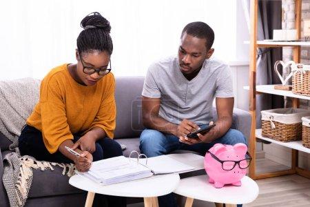 Photo pour Jeune couple africain assis sur le canapé Calcul de la facture - image libre de droit