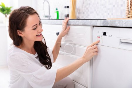 Photo for Side View Of A Happy Young Woman Pressing Button Of Dishwasher - Royalty Free Image