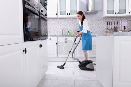 Photo for Young Female Janitor In Uniform Cleaning Kitchen Floor With Vacuum Floor - Royalty Free Image