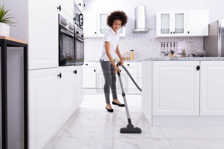 Photo for Close-up Of A Young Woman Cleaning The White Kitchen Floor With Vacuum Cleaner - Royalty Free Image