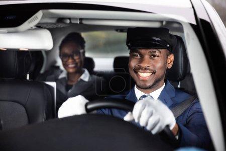 Photo pour Femme d'affaires Assis Derrière Happy African Homme Chauffeur Conduite Voiture - image libre de droit