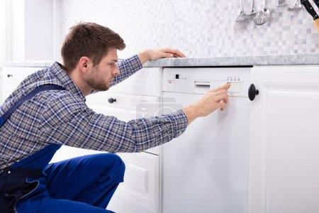 Photo for Young Serviceman Pressing Button Of Dishwasher In Kitchen - Royalty Free Image