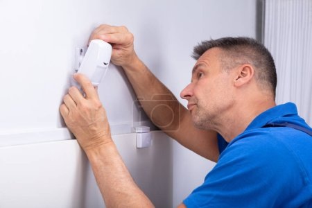 Photo for Close-up Of Male Electrician Installing Security System Door Sensor On Wall - Royalty Free Image