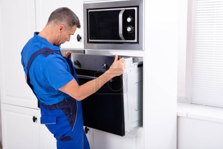 Photo for Male Technician Wearing Overall Installing Oven In Kitchen - Royalty Free Image