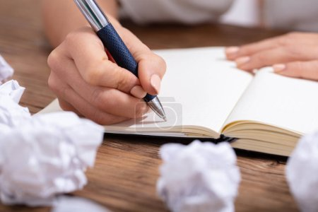 Photo for Close-up Of A Person Writing On Blank Notebook With Pen On Wooden Desk - Royalty Free Image