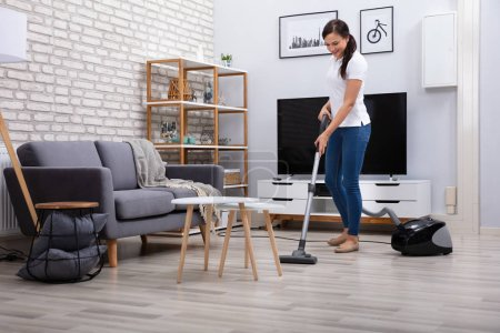 Photo for Happy Young Female Janitor Cleaning Floor With Vacuum Cleaner - Royalty Free Image