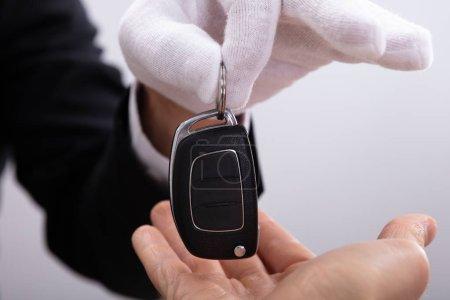 Photo pour Gros plan de la main de Valet donnant la clé de voiture à l'homme - image libre de droit